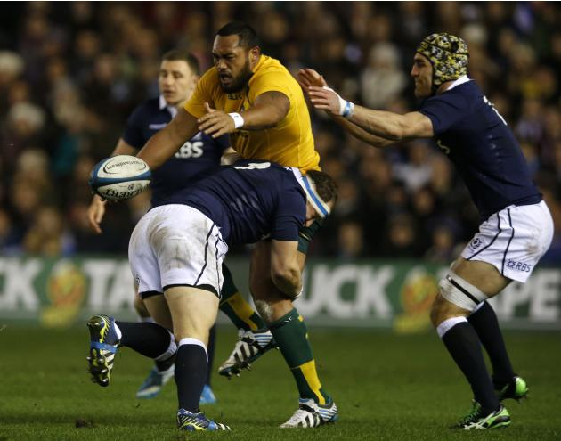 Australia's Sekope Kepu is tackled by Scotland's Moray Low during their rugby union international test match at Murrayfield Stadium in Edinburgh