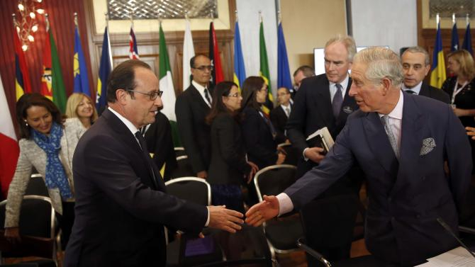Britain's Prince Charles and French President Hollande reach out their hands as French Environment Minister Royal looks on at the start of the Climate Action Special Executive Session at the Commonwealth Heads of Government Meeting (CHOGM) in Valletta