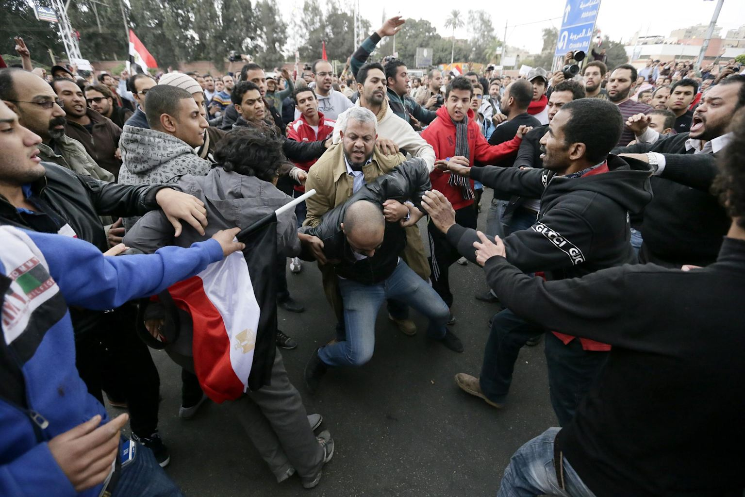 Egyptian President Mohammed Morsi's supporters beat an opponent, center, during clashes outside the presidential palace, in Cairo, Egypt, Wednesday, Dec. 5, 2012. Wednesday's clashes began when thousands of Islamist supporters of Morsi descended on the area around the palace where some 300 of his opponents were staging a sit-in.
