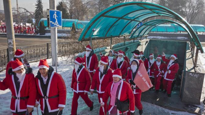 Revelers dressed as Father Frost, the equivalent of Santa Claus, walk out of an underpass during a parade in Almaty