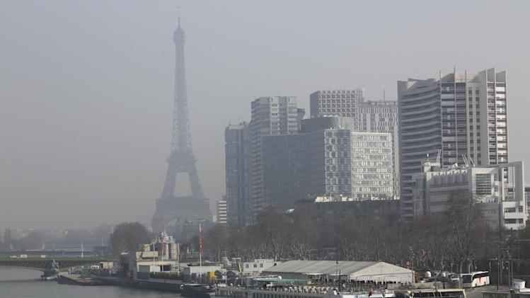 The Eiffel Tower and the Beaugrenelle district, right, are seen through the smog in Paris, Thursday March 13, 2014, as pollution over the French capital is at high levels. In an official effort intended to curb air pollution, Paris Town Hall announced that residential parking, will be free Thursday, to encourage drivers to leave their cars at home and take public transportation. (AP Photo/Remy de la Mauviniere)