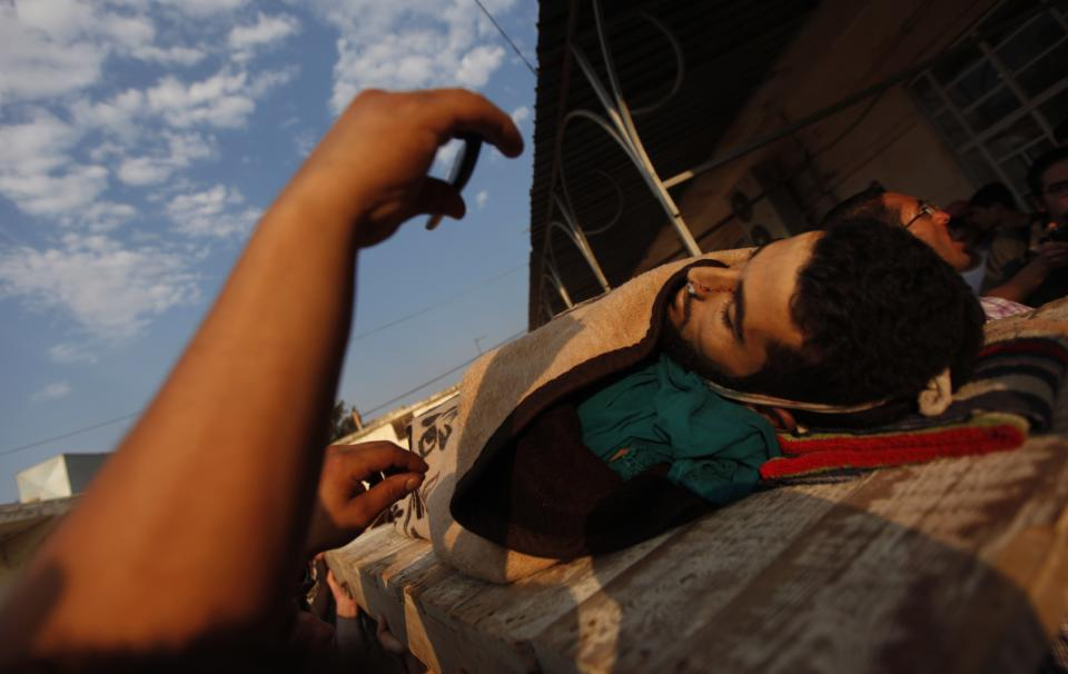 A Syrian man uses his mobile phone to photograph the body of  a 29 year-old Free Syria Army fighter, Husain Al-Ali, who was killed during clashes in Aleppo, during his funeral in the town of Marea on the outskirts of  Aleppo city, Syria, Thursday, Aug. 9, 2012. (AP Photo/ Khalil Hamra)