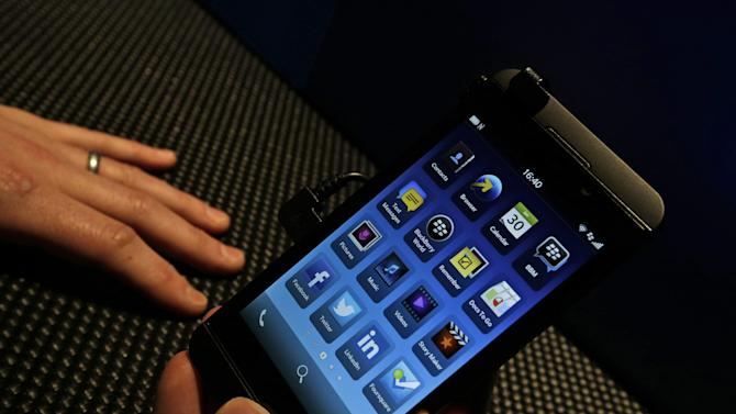 A man holds the new touchscreen BlackBerry Z10 smartphone, during a launch event for the new phone in London, Wednesday, Jan. 30, 2013.(AP Photo/Lefteris Pitarakis)