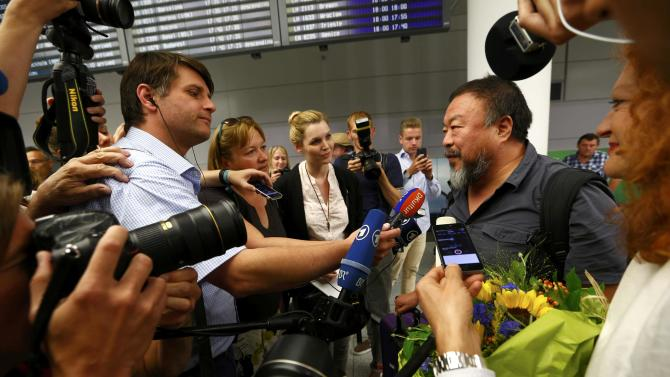 Dissident Chinese artist Ai Weiwei is surrounded by media as he arrives at the airport in Munich