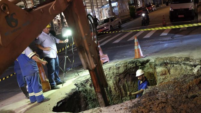 Employees of SABESP work on a pipe on the street after a water leakage in Sao Paulo