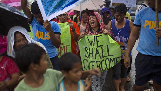 People march in the rain Tacloban, Philippines during a procession to call for courage and resilience among their Typhoon Haiyan survivors on Tuesday Nov. 19, 2013. Countless families lost loved ones to the typhoon. Hundreds of thousands of survivors have endured unimaginable suffering. Tacloban was filled with hopeless, fear-filled faces. Even now, blackened bodies with peeling skin still lay by the roads, or are trapped under the rubble. But as the crisis eases and aid begins to flow, hope is flickering. People smile, if only briefly, and joke, if only in passing. (AP Photo/David Guttenfelder)
