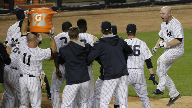 New York Yankees' Brian McCann, right, jumps into a crowd of teammates who greet him at home plate after McCann hit a three-run home run against the Tampa Bay Rays in the 12th inning of a baseball game, Friday, July 3, 2015, in New York. The Yankees won 7-5. (AP Photo/Julie Jacobson)