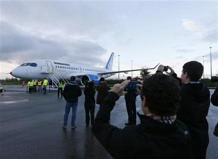 Bombardier employees and guests take photos of the CSeries aircraft prior to its first test flight in Mirabel, Quebec
