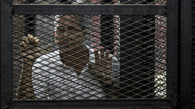 Al-Jazeera news channel's Australian journalist Peter Greste stands inside the defendants cage during his trial for allegedly supporting the Muslim Brotherhood on June 23, 2014 at the police institute near Cairo's Tora prison