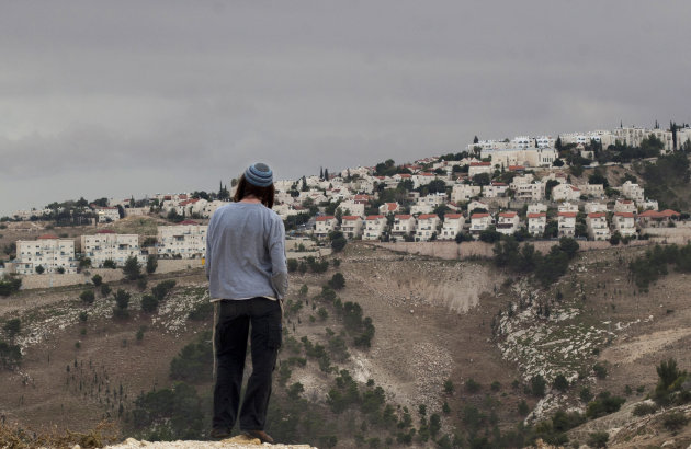A Jewish settler looks at the West bank settlement of Maaleh Adumim, from the E-1 area on the eastern outskirts of Jerusalem, Wednesday, Dec. 5, 2012. An Israeli-Palestinian showdown over plans for new Jewish settlements around Jerusalem escalated on Wednesday: Israel pushed the most contentious of the projects further along in the planning pipeline, while the Palestinian president said he would seek U.N. Security Council help to block the construction. (AP Photo/Sebastian Scheiner)