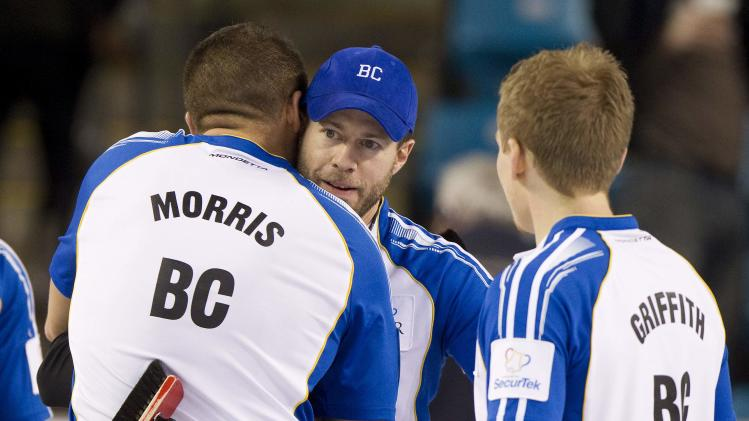 Team British Columbia skip John Morris celebrates with teammate Jim Cotter after defeating team Alberta in their draw at the 2014 Tim Hortons Brier curling championships in Kamloops, British Columbia