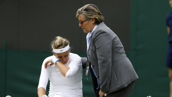 Victoria Azarenka of Belarus, left, is attended to after taking a fall during her Women's first round singles match against Maria Joao Koehler of Portugal at the All England Lawn Tennis Championships in Wimbledon, London, Monday, June 24, 2013. (AP Photo/Kirsty Wigglesworth)