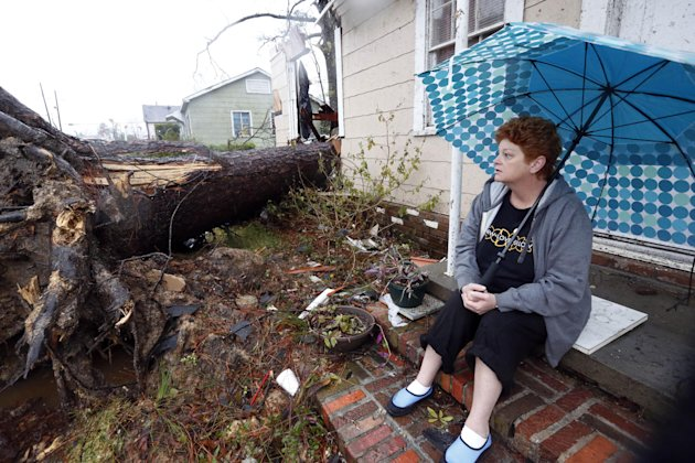 Hellen Chmiel, 57, sits in front of the remains of her home in Hattiesburg, Miss., Monday, Feb. 11, 2013, following a Sunday afternoon tornado that caused much damage throughout the South Mississippi college town. Chmiel, who was out of her house when the tornado struck, said the large pine tree in the front yard completely destroyed her bedroom. (AP Photo/Rogelio V. Solis)