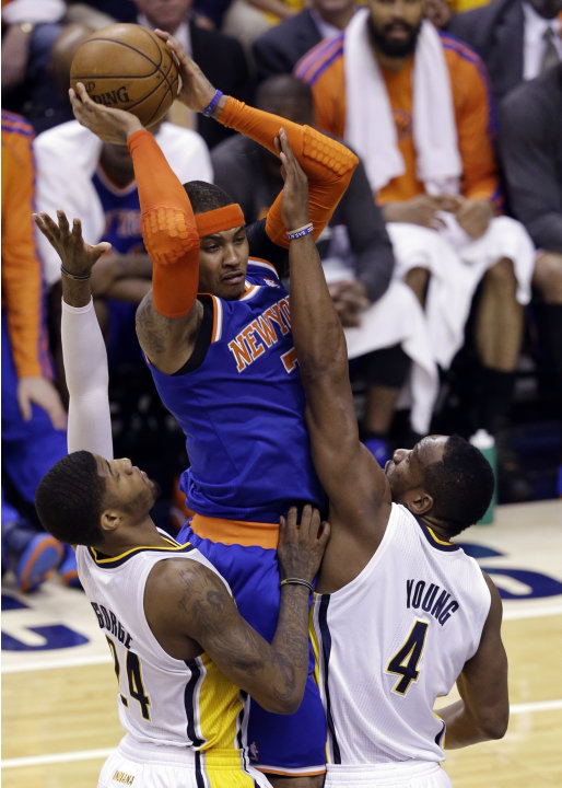 New York Knicks forward Carmelo Anthony, center, is forced to pass by Indiana Pacers forward Paul George, left, and forward Sam Young during the second quarter of Game 6 of the Eastern Conference semi