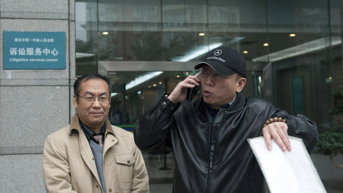 In this photo taken Thursday, Nov. 29, 2012, Li Zhuang, an ex-lawyer who claims he was framed and wrongfully jailed for 18 months, talks on his mobile phone in front of the Chongqing No. 1 Intermediate People's Court in southwest China's Chongqing Municipality.  At left is Yang Xuelin, Li's lawyer.  With China's new leaders freshly installed in power, authorities are turning their attention to tying up loose ends in the sprawling, scandal-ridden city once ruled by populist politician Bo Xilai before his downfall buffeted the leadership transition. In the past two weeks, authorities in Chongqing released Li, a lawyer disbarred after being convicted of having one of his clients lie in court, as well as a village official who had been sent to a labor camp for criticizing Bo. (AP Photo) CHINA OUT
