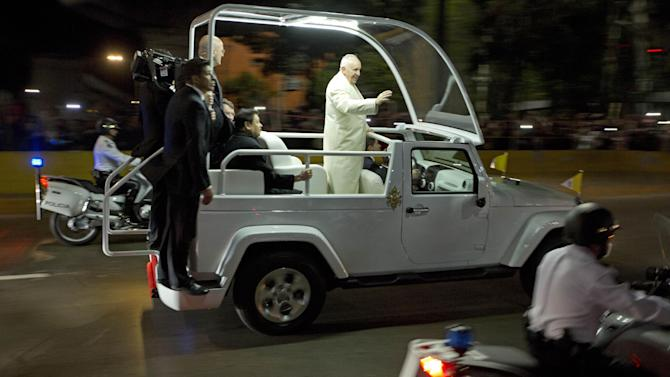 Pope Francis waves to people from the popemobile along his route to the Apostolic Nunciature, the Vatican's diplomatic mission, in Mexico City, Friday, Feb. 12, 2016. The pontiff is in Mexico for a week-long visit. (AP Photo/Moises Castillo)