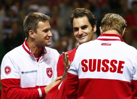 Federer celebrates with Chiudinelli and Lammer after winning his Davis Cup semi-final tennis match against Fognini at the Palexpo in Geneva