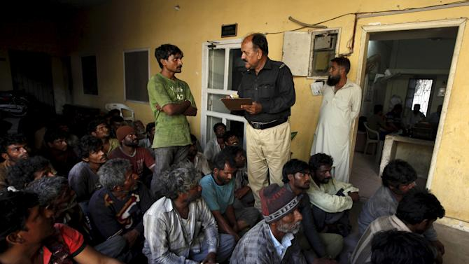 A policeman inquires details from a fisherman from India, after being detained with others in Pakistani waters, at a police station in Karachi