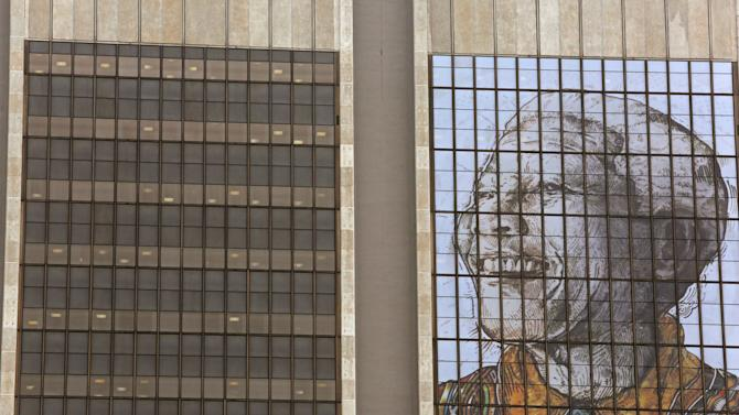 A portrait representing former president Nelson Mandela on the windows of a building in downtown Cape Town, South Africa, Monday June 24, 2013. Former South African president Nelson Mandela remains in critical condition in a Pretoria hospital, President Jacob Zuma told journalists at a packed press briefing Monday, calling on people to pray for his recovery and the media not to demand details of his treatment or condition. (AP Photo/Schalk van Zuydam)