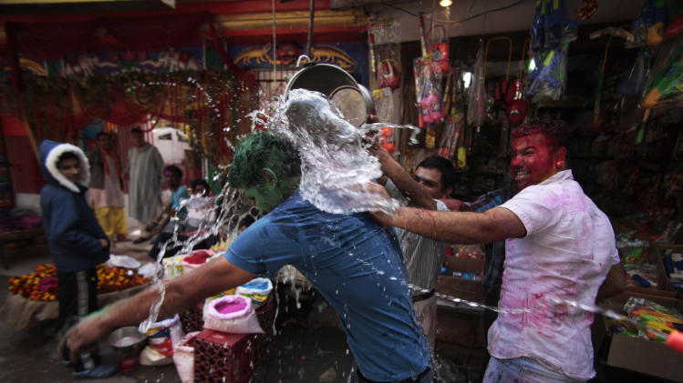 A man pours water over another during Holi festival celebrations in Jammu, India, Sunday, March 16, 2014. Holi, the festival of colors celebrates the arrival of spring among other things.(AP Photo/Channi Anand)