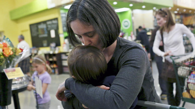 In this Feb. 8, 2014 photo, Nicole Dimetman kisses her son while waiting in the checkout line at Whole Foods in Austin, Texas A federal judge is expected to hear arguments Wednesday, Feb. 12, 2014, in a lawsuit brought by two homosexual couples who say the Texas Constitution's ban on gay marriage is unconstitutional because it denies them the right to be treated like everyone else. (AP Photo/The San Antonio Express-News, Lisa Krantz) RUMBO DE SAN ANTONIO OUT; NO SALES; MAGS OUT