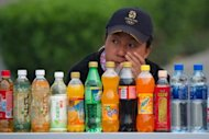 <p>A woman sells soft drinks at a stall in Beijing on April 22. Men who drink one normal-sized soft drink per day are at greater risk of getting more aggressive forms of prostate cancer, according to a Swedish study released Monday.</p>