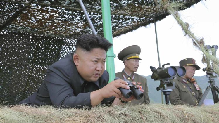 North Korean leader Kim Jong Un holds binoculars as he guides a live-firing exercise in this undated photo released by North Korea's KCNA in Pyongyang