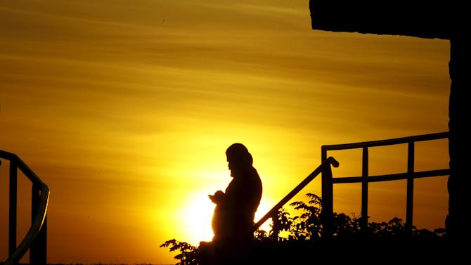 A Cuban migrant looks at a mobile phone as the sun sets in the town of La Cruz