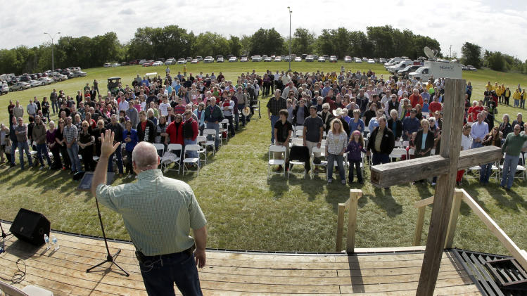 Pastor John Crowder delivers a sermon during a service for the First Baptist Church held in a field Sunday, April 21, 2013, four days after an explosion at a fertilizer plant in West, Texas. The church could not meet in their building because it was in a damage zone after a massive explosion at the West Fertilizer Co. Wednesday night that killed 14 people and injured more than 160. (AP Photo/Charlie Riedel)