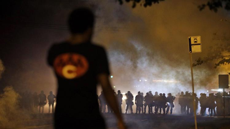 FILE - In this Aug. 13, 2014 file photo, a man watches as police walk through a cloud of smoke during a clash with protesters in Ferguson, Mo. The response to Brown's death turned violent because of a convergence of factors, observers said. (AP Photo/Jeff Roberson, File)