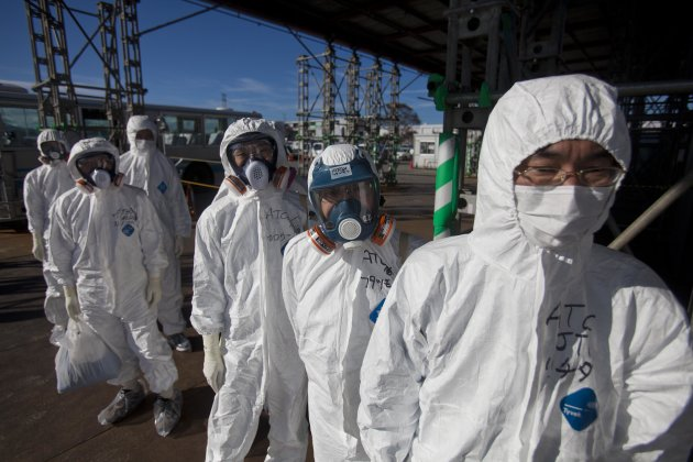 FILE - In this Saturday, Nov. 12, 2011 file photo, workers in protective suits and masks wait to enter the emergency operation center at the crippled Fukushima Dai-ichi nuclear power station in Okuma,