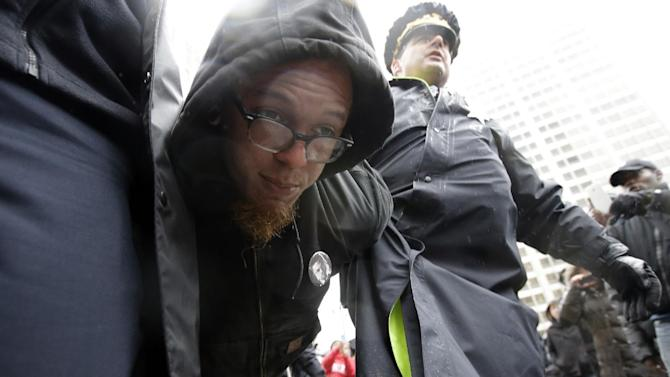 "A man is detained near Pioneer Court as a collection of elected officials on Friday, Nov. 27, 2015, in Chicago. Community activists and labor leaders hold a demonstration billed as a ""march for justice"" in the wake of the release of video showing an officer fatally shooting Laquan McDonald. (AP Photo/Nam Y. Huh)"