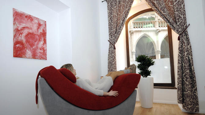 In this picture taken Tuesday, Feb. 5, 2013 a woman rests at the Reflexia studio in Vienna, Austria. One sleepy little side street in Vienna just got sleepier. Tucked away behind a Gothic church and surrounded by Renaissance-era houses, the new studio is offering deal-makers, movers and shakers and foot-sore tourists respite at a price — a half-hour power nap for 11 euros (US dollar 15). (AP Photo/Hans Punz)