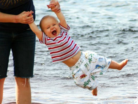 baby mom swinging ocean playing laughing happy
