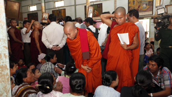 Myanmar Buddhist monks comfort refugees, following the ethnic unrest between Buddhists and Muslims, as they visit a monastery along with Vijay Nambiar, unseen, U.N. Secretary General Ban Ki-moon's special adviser on Myanmar, in Meikhtila, about 550 kilometers (340 miles) north of Yangon, Myanmar, Sunday, March 24, 2013. The top UN envoy to Myanmar toured a central city Sunday destroyed in the country's worst explosion of Buddhist-Muslim violence this year, calling on the government to punish those responsible for a tragedy that left dozens of corpses piled in the streets, some of them charred beyond recognition. (AP Photo/Khin Maung Win)