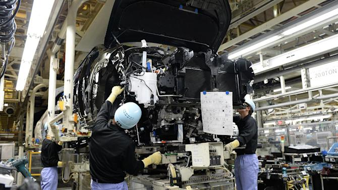 Employees of Toyota Motor Kyushu mount an engine into the body of a Lexus NX on an assembly line at the Miyata plant in Fukuoka Prefecture, Japan on August 8, 2014