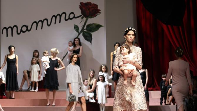 A model holding a child presents a creation from the Dolce & Gabbana Autumn/Winter 2015/16 collection during Milan Fashion Week