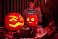 A man smiles after putting a candle in his carved pumpkin at a pumpkin carving competition at the Helix Lounge in Washington on October 26, 2011. Poland's powerful Roman Catholic church has raised the alarm about the growing influence of what it brands satanic rituals during Halloween