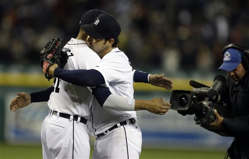 Detroit Tigers starting pitcher Anibal Sanchez, center, hugs teammate Victor Martinez, left, after the last out in the ninth inning of a baseball game against the Minnesota Twins in Detroit, Friday, M