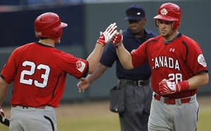 Canada's Cole Armstrong, right, high fives teammate Marcus Knecht at the Baseball World Cup in Panama City, in this Oct. 8, 2011 photo. Armstrong gave up his leg to get Canada to the World Baseball Classic. Despite a ruptured Achilles tendon, he refused to leave the dugout as Canada went on to beat Germany 16-7 in September. THE CANADIAN PRESS/AP, Andres Leighton
