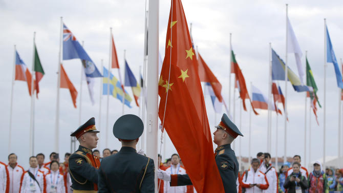Russian soldiers raise China's flag as the Chinese Olympic delegation watches during a team welcoming ceremony before the 2014 Winter Olympics, Wednesday, Feb. 5, 2014, in Sochi, Russia. (AP Photo/Vadim Ghirda)