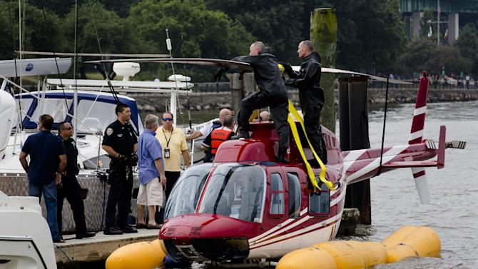A helicopter rests on a pontoon at the 79th Street Boat Basin after an emergency landing over the Hudson river, Sunday, June 30, 2013, in New York. New York authorities say a helicopter carrying four Swedish tourists landed in the Hudson River off Manhattan Sunday, but everyone has been rescued. (AP Photo/John Minchillo)