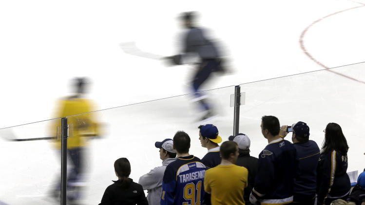 Fans watch as members of the St. Louis Blues take part in their first practice of NHL hockey training camp Sunday, Jan. 13, 2013, in St. Louis. The Blues will open their season at home Jan. 19, against the Detroit Red Wings. (AP Photo/Jeff Roberson)