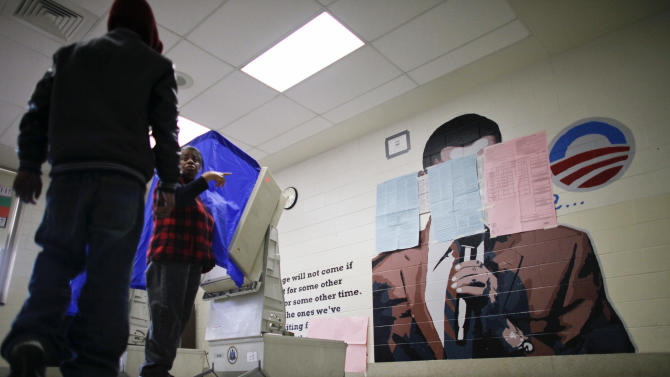 People cast their votes Tuesday, Nov. 6, 2012, at polling location inside the Benjamin Franklin Elementary School in Northeast Philadelphia, where a mural of President Barack Obama painted on a wall behind two voting booths was ordered covered up by a Philadelphia court. The mural had been left uncovered when the polling location opened, but was ordered covered after Republicans filed a complaint. (AP Photo/ Joseph Kaczmarek)