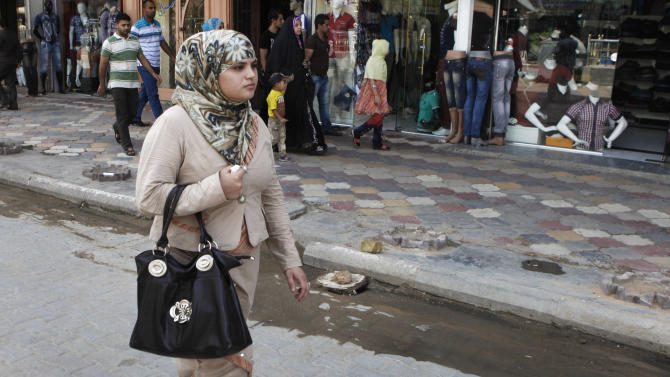 An Iraqi woman walks past shops at a marketplace in Kazimiyah neighborhood, northern Baghdad, Iraq, Sunday, Sept. 2, 2012.  A new culture rift is emerging in Iraq and, largely, at the seat of one of Shiite Islam's holiest sites as young women doff their shapeless cover ups and men strut around in revealing slacks and edgy haircuts. This has prompted clerics to mobilize the fashion police in the name of protecting the Islamic nation's heritage. (AP Photo/Karim Kadim)