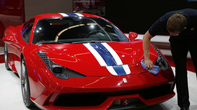 A man cleans a Ferrari 458 Speciale during the second press day of the 65th Frankfurt Auto Show in Frankfurt, Germany, Wednesday, Sept. 11, 2013. More than 1,000 exhibitors will show their products to the public from Sept. 12 through Sept.22, 2013. (AP Photo/Frank Augstein)