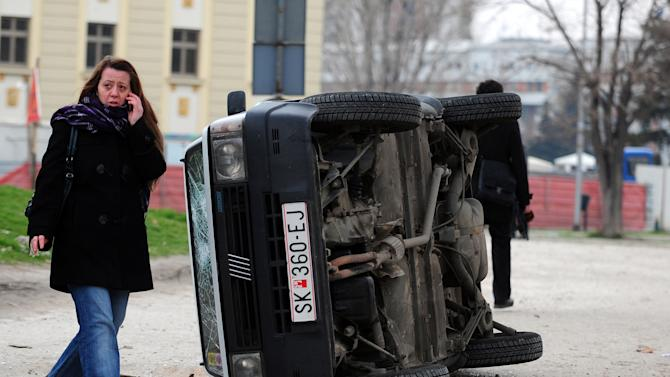 A woman passes beside a demolished vehicle during a violent protest of a group of ethnic Albanians in Skopje, Macedonia, Saturday, March 2, 2013. Hundreds of ethnic Albanians staged a contra-protest on Saturday to express support for the designation of the new defense minister. Police said Saturday at least 20 people, from whom 13 police officers and other mainly youngsters were injured in a series of scuffles that erupted late on Friday and continued over night when a group of a few hundred Macedonians started a protest against the designation of a new defense minister Talat Xhaferi, an ethnic Albanian and former rebel commander. (AP Photo/Vangel Tanurovski)