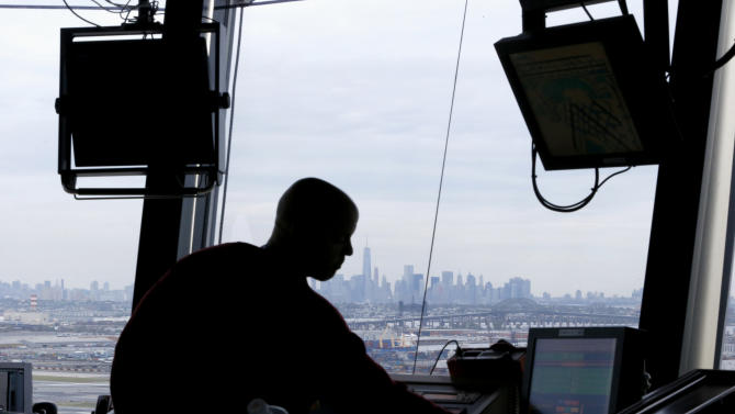 FILE - In this May 21, 2015 file photo, an air traffic controller works in the tower at Newark Liberty International Airport in Newark, N.J. A chronic shortage of controllers has reached a crisis that will lead to widespread flight delays if left unchecked, officials for the union that represents air traffic controllers said Tuesday.  (AP Photo/Julio Cortez, File)