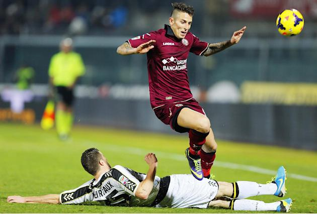 Udinese's Thomas Heurtaux, of France, on the ground, slides in to tackle Livorno's Leandro Greco during a Serie A soccer match between Livorno and Udinese, in Leghorn, Italy, Saturday, Dec. 21
