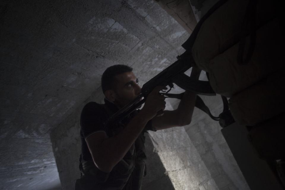 In this Sunday, Sept. 23, 2012 photo, a Free Syrian Army fighter shoots his weapon against Syrian army positions in the al Izaa district in Aleppo, Syria. (AP Photo/ Manu Brabo)